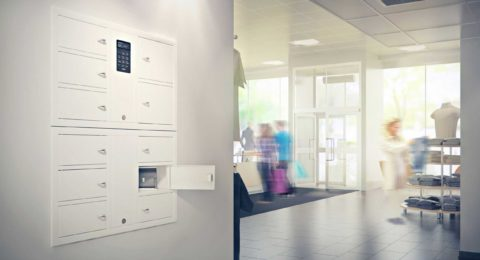 Valuables cabinet 7004 S in the System series with a 7006 S in the Expansion series. Mounted in a wall recess with one compartment open containing a bag in a shop premises.