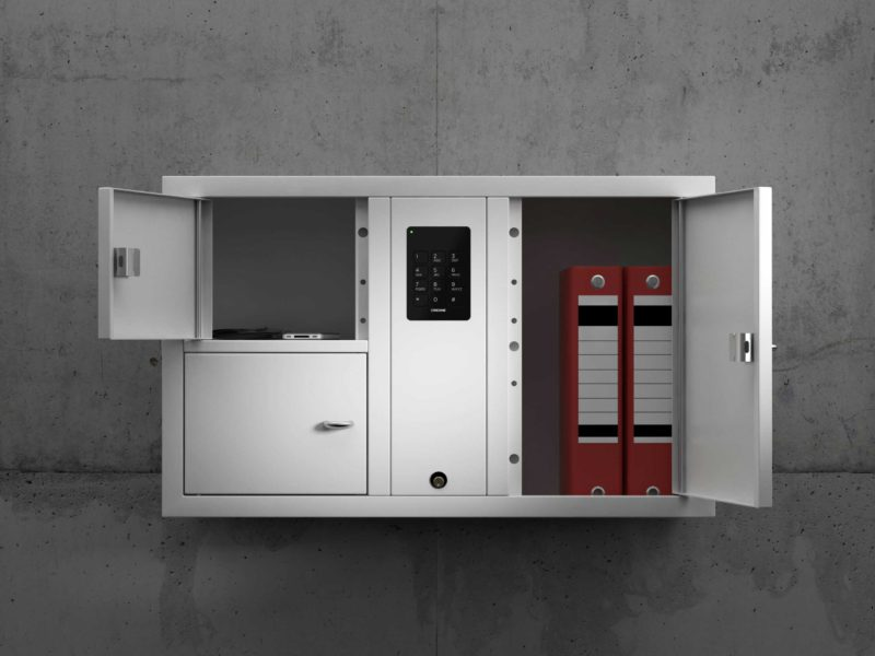 Valuables cabinet 7003 S in the System series. Mounted on the wall with open compartments containing folders, telephone and wallet.
