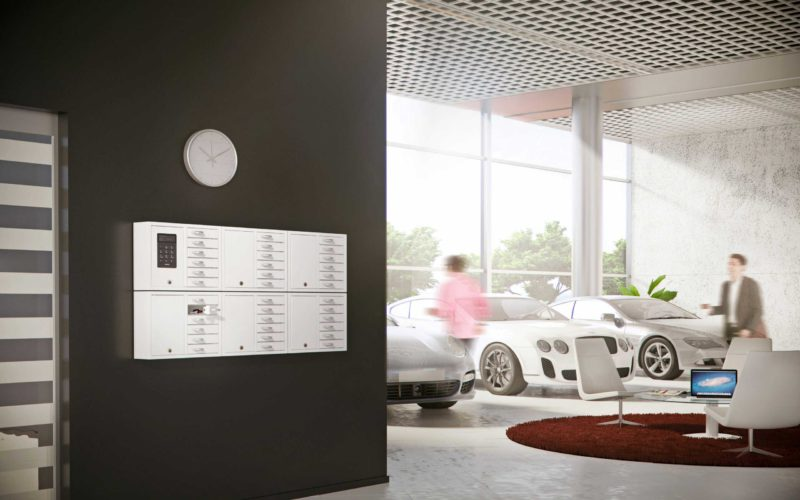 The 9006 S key cabinet from the System series plus five of the 9006 E from the Expansion series is handling the car company's key management. Mounted on the wall with open compartments containing car keys.