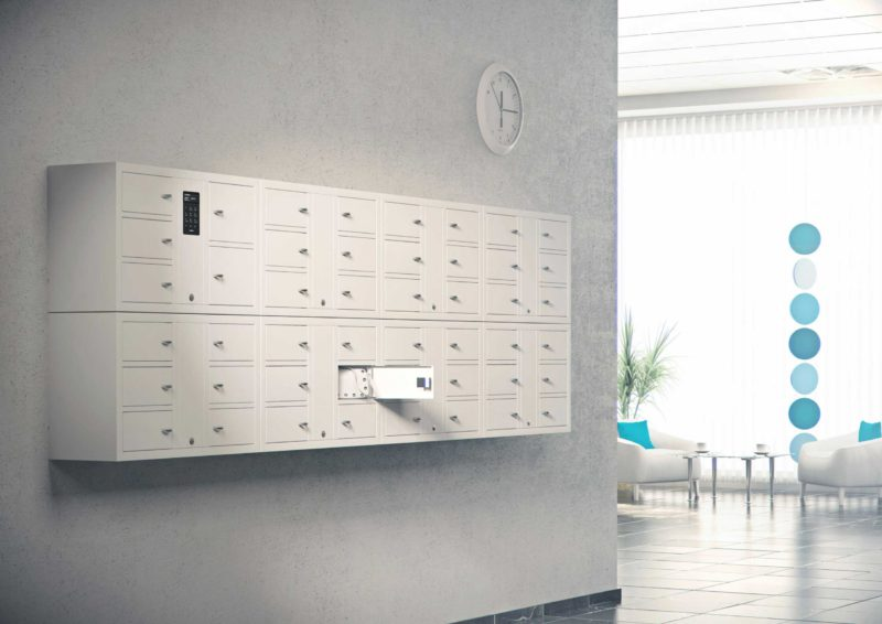 Valuables cabinet 7004 S in the System series with seven of the 7006 S in the Expansion series. Mounted on a wall with one compartment open containing a bag in a lounge.