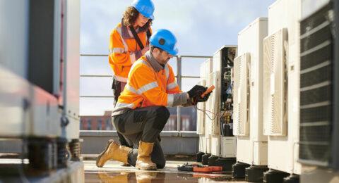 Deux personnes qui effectuent un travail de maintenance accèdent aux clés par l'intermédiaire d'un système électronique de stockage et de gestion des clés